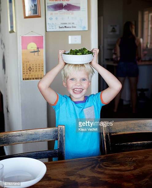 Boy standing with bowl of salad on his head