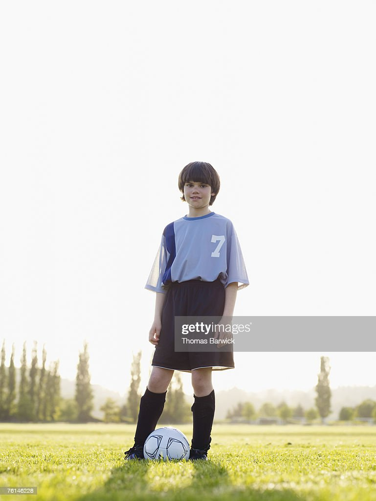 Boy (12-13) standing with football at feet in field : Stock Photo