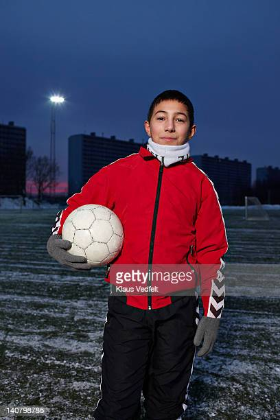 Boy standing with football on soccerfield