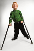 Boy standing with forearm crutches