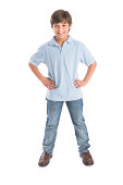 Full length portrait of happy little boy standing with hands on hip against white background