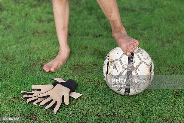 Boy standing with his foot on a football