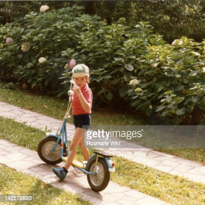 Boy standing with his new scooter in garden : Photo