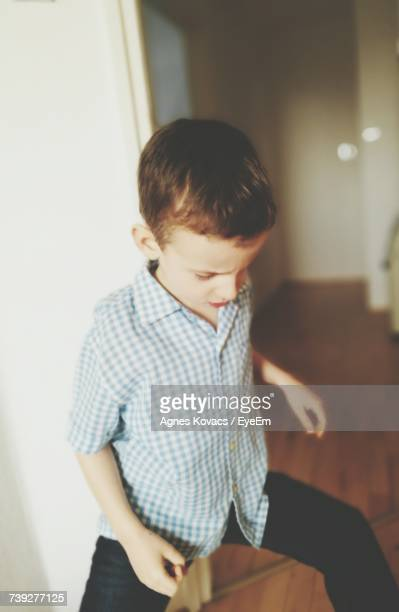 Boy Standing With Legs Apart At Home