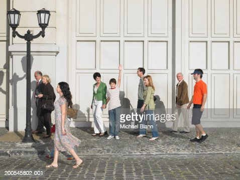 Boy (11-13) standing with mother in street, raising hand, portrait