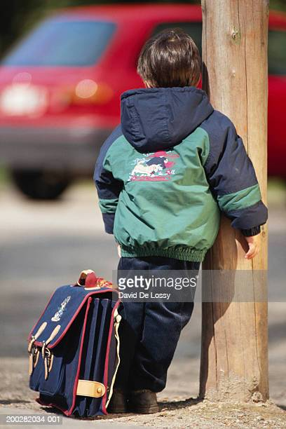 Boy (6-7) standing with satchel, rear view