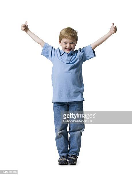 Boy standing with thumbs up smiling