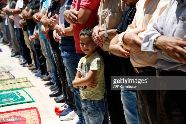 A boy stands among Palestinian Muslim worshippers performing Friday noon prayer in the AlAqsa mosque compound in Jerusalem's old city on August 4...