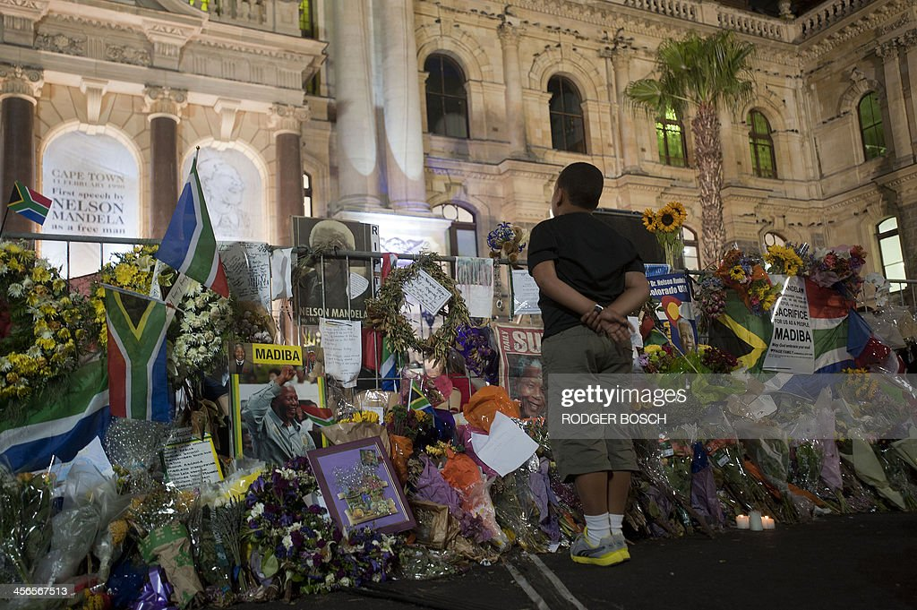 A boy stands amongst flowers and messages left in memory of late South African former president Nelson Mandela at a night vigil in front of the Cape Town City Hall, on December 14, 2013, in Cape Town. Nelson Mandela's remains were returned to his beloved rural childhood village ahead of a traditional burial on Sunday, the final leg of his exceptional 95-year journey. Mandela, the revered icon of the anti-apartheid struggle in South Africa and one of the towering political figures of the 20th century, died in Johannesburg on December 5 at age 95. AFP PHOTO/RODGER BOSCH