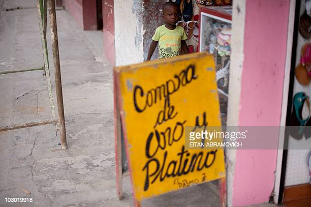 A boy stands behind a sign that says 'We buy gold and platinum' in downtown Tado Choco department Colombia on July 8 2010 In Tado in the community of...