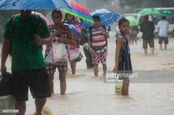 A boy stands beside the residents wading the streets in Provident village in Marikina on Friday Heavy downpours and flooded rivers brought by...