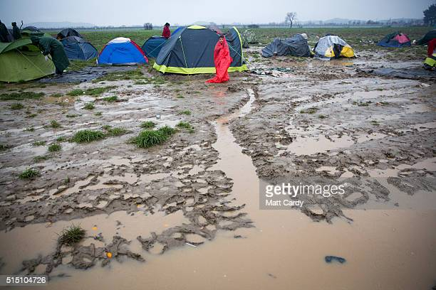 A boy stands besides his tent as rain falls at the Idomeni refugee camp on the Greek Macedonia border on March 12 2016 in Idomeni Greece The decision...