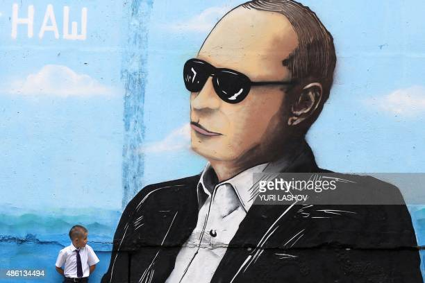 A boy stands by a wall sprayed with a graffiti depicting Russia's President Vladimir Putin in the Crimean city of Simferopol on September 1 2015 /...