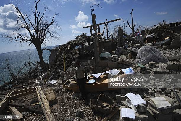 A boy stands in a home destroyed by Hurricane Matthew in Port Salut southwest of PortauPrince on October 11 2016 Haiti faces a humanitarian crisis...