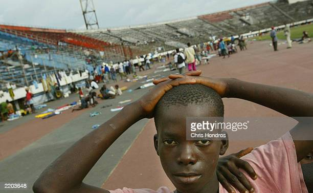A boy stands in a sports stadium taken over by refugees July 25 2003 in Monrovia Liberia Aid workers warn of a humanitarian catastrophe if fighting...