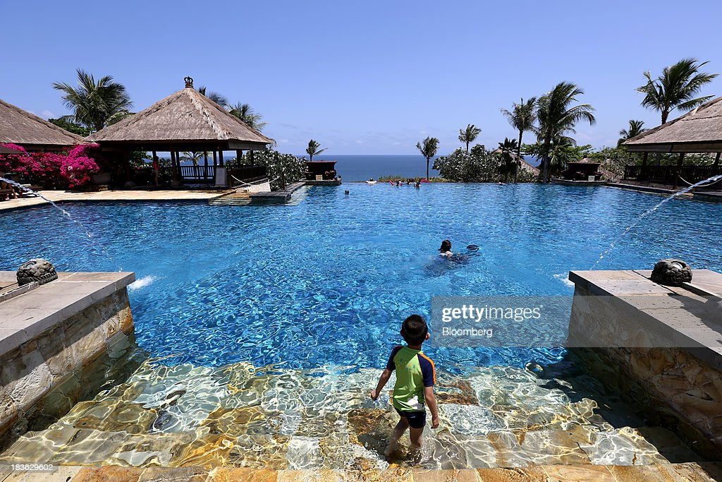 A boy stands in a swimming pool at the Ayana Resort and Spa hotel in Jimbaran, Bali, Indonesia, on Saturday, Oct. 5, 2013. Indonesia's central bank kept its key interest rate unchanged after its most aggressive tightening cycle in almost eight years as inflation pressure eased. Photographer: SeongJoon Cho/Bloomberg via Getty Images