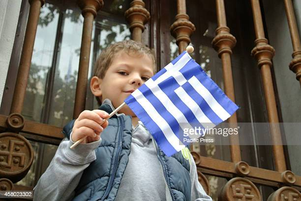 A boy stands in a window waving a Greek flag while watching the parade Greek people celebrate the National OHI day that marks the anniversary of the...