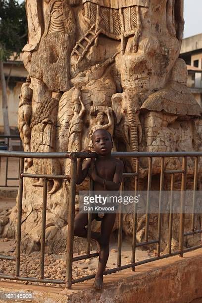 A boy stands in front of a tree with carvings that tell the story of the slave trade in the centre of Ouidah on January 8 2012 in Ouidah Benin Ouidah...
