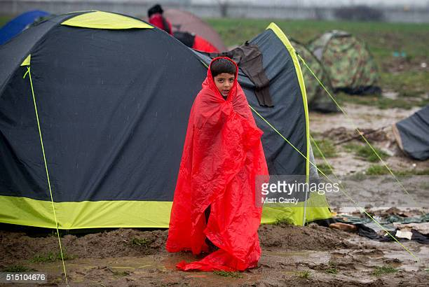 A boy stands in the rain besides his tent as rain falls at the Idomeni refugee camp on the Greek Macedonia border on March 12 2016 in Idomeni Greece...