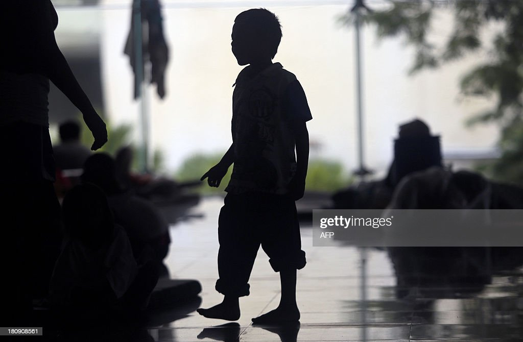 A boy stands inside a shelter in Acapulco, state of Guerrero, Mexico, on September 17, 2013 as heavy rains hit the country. Mexican authorities scrambled Tuesday to launch an air lift to evacuate tens of thousands of tourists stranded amid floods in the resort of Acapulco following a pair of deadly storms. The official death toll rose to 47 after the tropical storms, Ingrid and Manuel, swarmed large swaths of the country during a three-day holiday weekend, sparking landslides and causing rivers to overflow in several states.