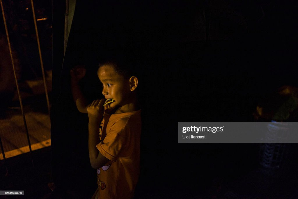 A boy stands inside temporary shelters in East Jakarta district on January 18, 2013 in Jakarta, Indonesia. According to the National Disaster Management Agency, about 50 percent of the capital is under water following the floods which have so far claimed eleven lives and displaced thousands of Indonesians.