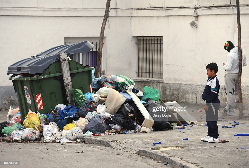 A boy stands near a pile of uncollected garbage during the 20th day of the garbage collectors strike on November 21, 2012 in Jerez de la Frontera, Spain. The garbage collectors are protesting planned layoffs in the sector by the local town council.