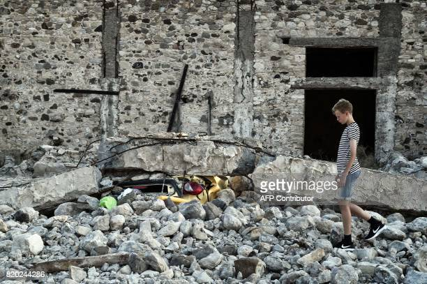 A boy stands next to a car crushed under rubble near the port of the Greek island of Kos following a 65 magnitude earthquake which struck the region...