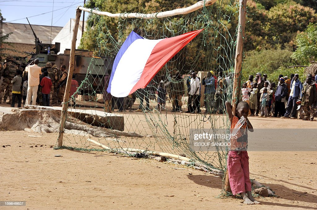 A boy stands next to a French national flag hung on a goalpost as French soldiers arrive in the Malian town of Diabaly, on January 21, 2013. French and Malian troops today recaptured the Malian towns of Diabaly and Douentza from Islamist fighters, France's defence minister said.French and Malian troops earlier today entered Diabaly, which has been the theatre of air strikes and fighting since being seized by Islamists a week ago, an AFP journalist witnessed.