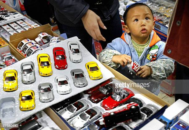 A boy stands next to car models displayed at a toy store in Chengdu in China's southwestern province of Sichuan 31 October 2007 US legislators...