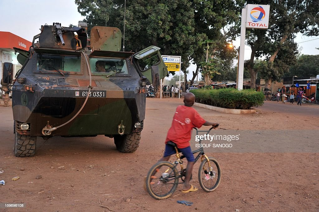 A boy stands next to French soldiers patroling in an armoured vehicle on January 18, 2013 in Markala. France confirmed today that Malian troops had taken control of the key central town of Konna from armed Islamists who seized the country's vast desert north in April last year
