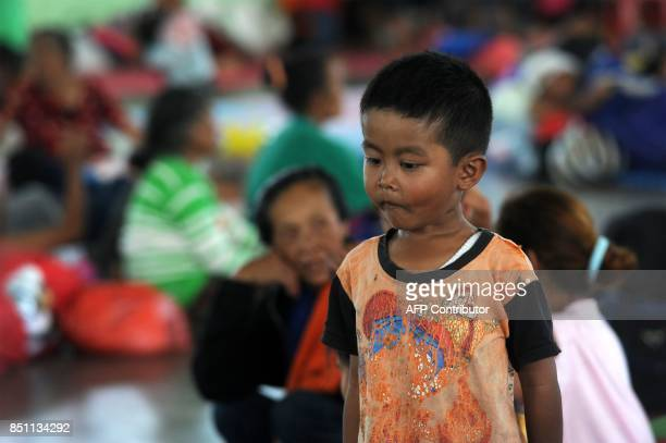 A boy stands next to villagers evacuated during the raised alert levels for the volcano on Mount Agung in Klungkung regency on the Indonesian resort...