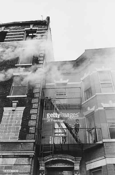 A boy stands on a fire escape as smoke passes from a fire in the next building New York City 1975