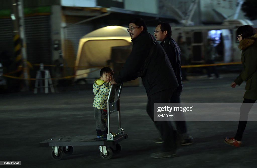 A boy stands on a trolley as his father pushes it to leave the earthquake site as rescue personnel continue work on a collapsed building in the southern Taiwanese city of Tainan on February 6, 2016 following a strong 6.4-magnitude earthquake. A powerful earthquake in Taiwan felled a 16-storey apartment complex full of families who had gathered for Lunar New Year celebrations in the early hours of February 6, with at least seven dead and more than 30 feared trapped. AFP PHOTO / Sam Yeh / AFP / SAM YEH