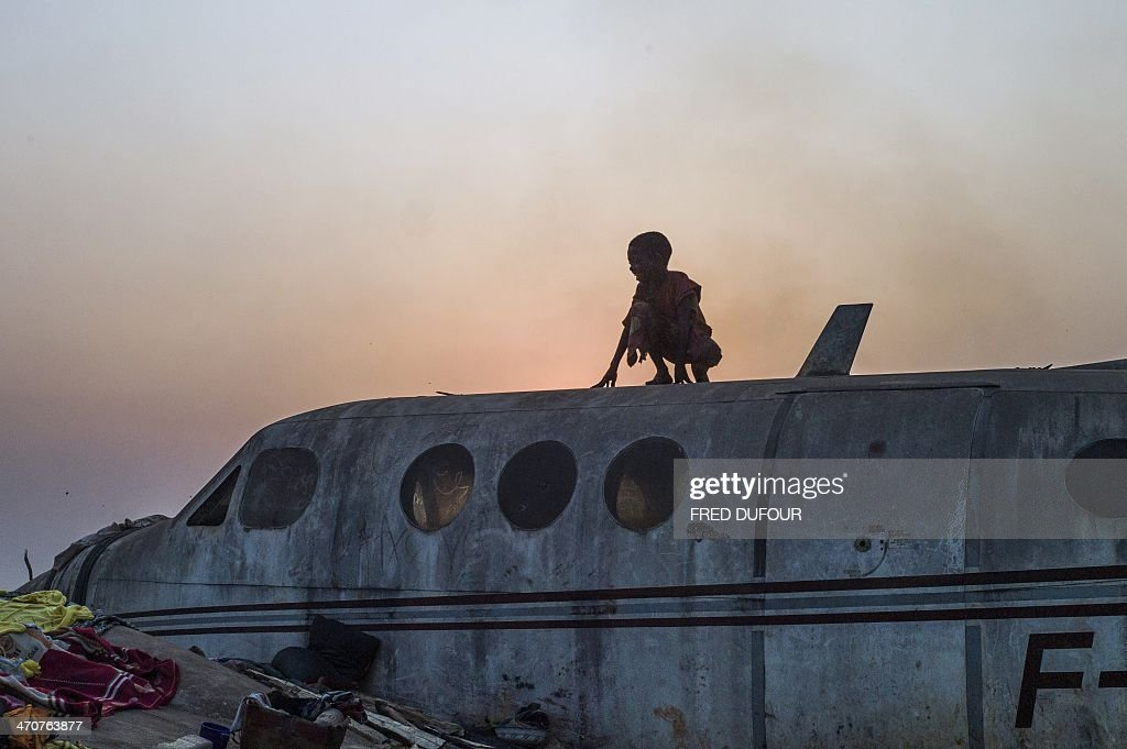 A boy stands on an airplane in the Christian Mpoko refugee camp on February 20, 2014 during sunset, in Bangui, Central African Republic. Interim President Samba Panza has vowed to 'go to war' on the anti-balaka, who claim to seek vengeance for atrocities committed by a mainly Muslim rebel alliance, the Seleka, which temporarily seized power in March last year. The Seleka coup plunged the country into chaos, unleashing a wave of Muslim-Christian violence that has left thousands dead. Hundreds of thousands of people have also been displaced by the brutal surge of killings, mutilations, rapes and looting.