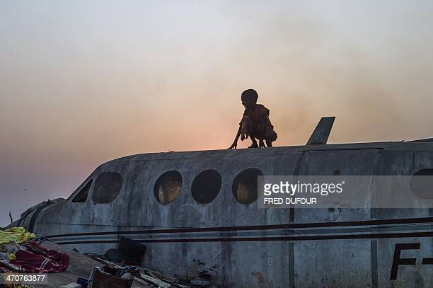 A boy stands on an airplane in the Christian Mpoko refugee camp on February 20 2014 during sunset in Bangui Central African Republic Interim...