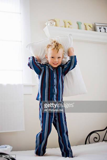 Boy stands on bed ready to throw pillow