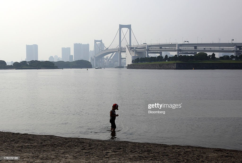 A boy stands on the beach across from the Rainbow Bridge in the Odaiba area of Tokyo, Japan, on Monday, Aug. 12, 2013. Japan's economy slowed more than forecast in the second quarter as businesses cut investment, undermining gains in consumer and government spending that helped reduce deflationary pressures. Photographer: Tomohiro Ohsumi/Bloomberg via Getty Images