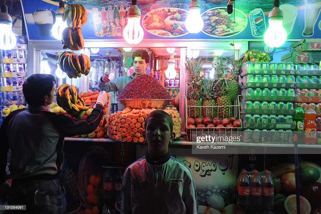 A boy stands outside a fruit juice parlor in the early hours of evening on October 16, 2011 in Kabul, Afghanistan.