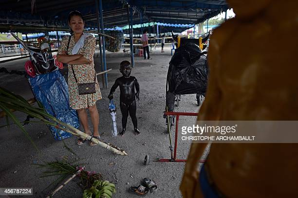 A boy stands with his body painted in black before riding a mock buffalo during a parade ahead of the annual buffalo races in Chonburi southeast of...