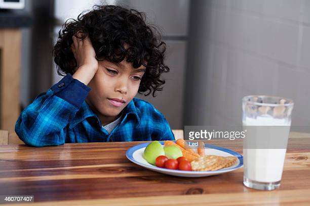 Boy staring at snacks and glass of milk