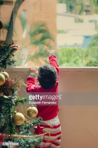Boy staring out of window on Christmas eve