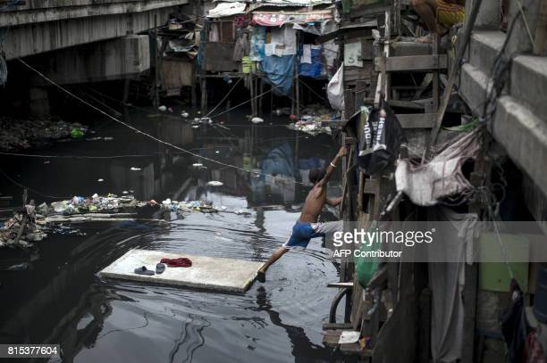A boy steps off a makeshift boat made from styrofoam at the Estero de Vitas in Tondo in Manila on July 16 2017 The Philippine economy has sustained...