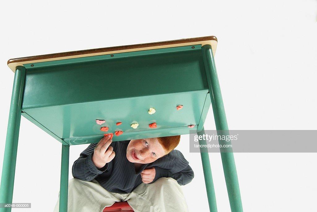 Boy Sticking Gum Under Desk : Stock Photo
