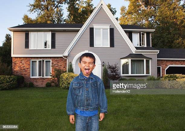 boy sticking out tongue in front of house