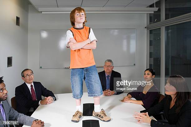 A boy stood on a table in a boardroom