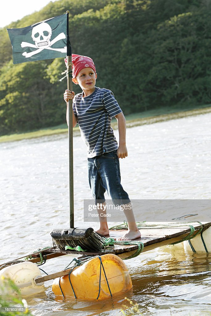 Boy stood on home made raft dressed as pirate : Stock Photo