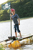 Boy stood on home made raft dressed as pirate