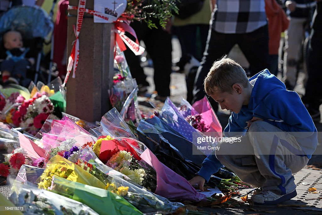 A boy stops to look at flowers as he attend a local community memorial vigil outside Ely Fire Station for 32-year-old, Karina Menzies, who was killed in a hit-and-run collision on October 21, 2012 in Cardiff, Wales. Detectives are questioning a 31-year-old man arrested on suspicion of murder after a series of hit-and-runs in Cardiff that left a woman dead and 13 people injured. Nine casualties, five of them children, are still in hospital. Two adults are in critical but stable conditions.
