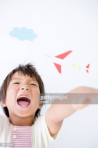 Boy stretching arms, shouting front of wall