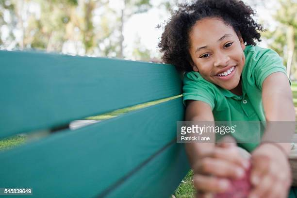Boy stretching on bench in park